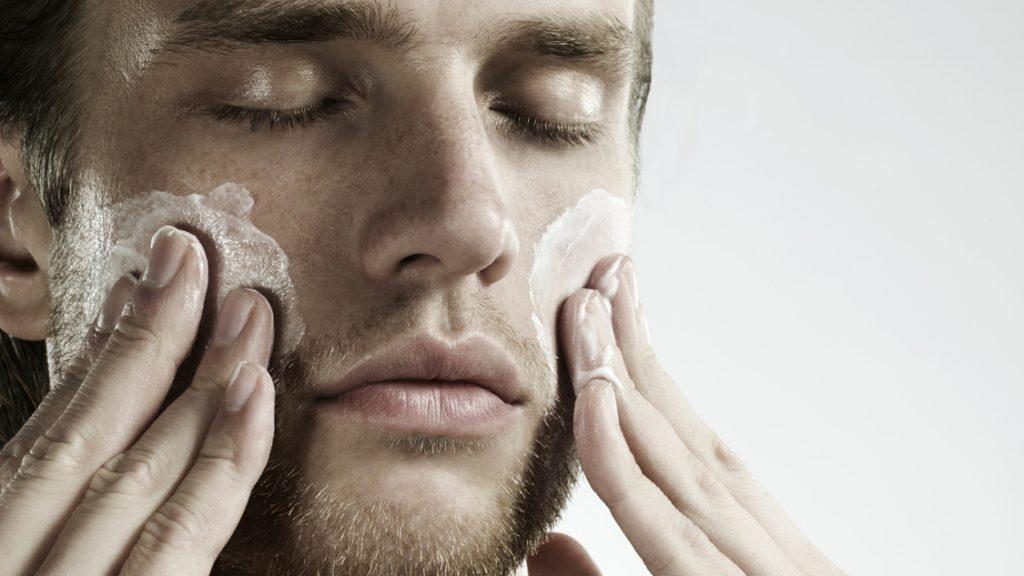 portrait of man applying moisturizer to face